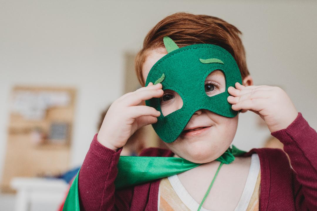 Jourhem sökes! Bilden visar en pojke som kollar in i kameran. Han har en grön superhjälte mask på sig.